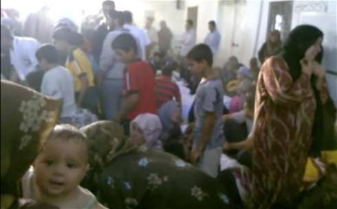 """Famiglie attorno i corpi delle vittime di violenza compiuto in Tremseh dalle forze di milizia note come """"Shabiha"""" (foto AP)"""