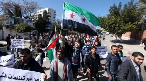 Palestinian students wave Syrian flags during a march in Gaza City.