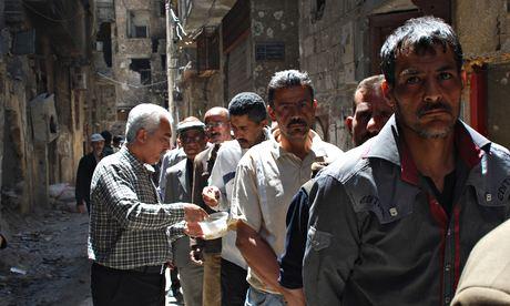 Palestinesi nel campo profughi assediati aspettano in fila per ottenere un po' di cibo.  L'Onu è rimasto bloccato fuori il campo di Yarmouk (Damasco) per più di 2 settimane.