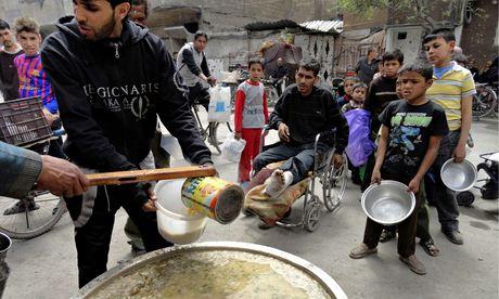 Volontari distribuiscono cibo gratuitamente ai residenti del campo profughi di Yarmouk, Siria.